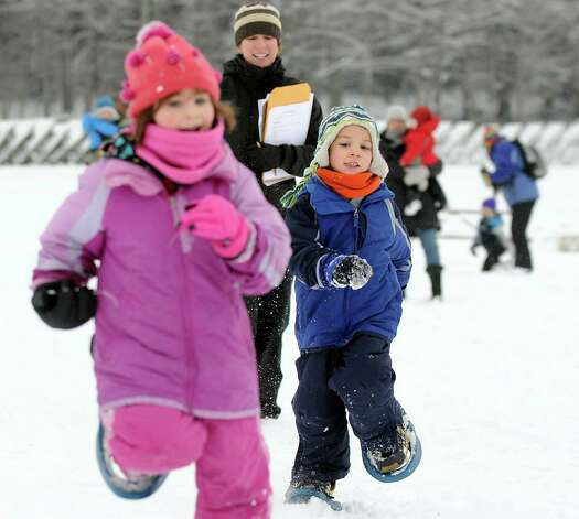 Ryan Phelan, 6, of Poestenkill, right, tries to catch his cousin Madelyn Charron, 5, left, in a snowshoe race during the 30th annual Winter Festival on Saturday, Jan. 24, 2015, at Grafton Lakes State Park in Grafton, N.Y. Volunteer Susan Stiner, center, judged the race. The event also featured ice fishing, hockey, hikes, games for kids and a polar plunge. (Cindy Schultz / Times Union) Photo: Cindy Schultz / 00030277A