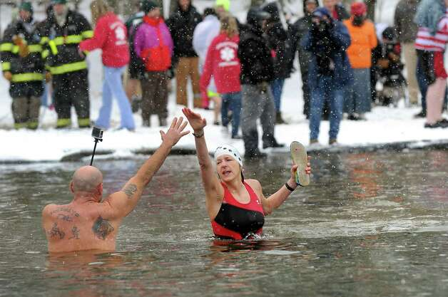 Cheryl Mugno of West Sand Lake, center, high fives John Perry of Johnsonville as they take the polar plunge into Long Pond during the 30th annual Winter Festival on Saturday, Jan. 24, 2015, at Grafton Lakes State Park in Grafton, N.Y. The event also featured ice fishing, hockey, hikes and games for kids. (Cindy Schultz / Times Union) Photo: Cindy Schultz / 00030277A