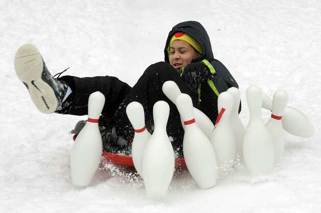 Peter Konteh, 10, of Watervliet slides into bowling pins and hits a strike at snow bowling during the 30th annual Winter Festival on Saturday, Jan. 24, 2015, at Grafton Lakes State Park in Grafton, N.Y. The event also featured ice fishing, hockey, hikes, games for kids and a polar plunge. (Cindy Schultz / Times Union) Photo: Cindy Schultz / 00030277A