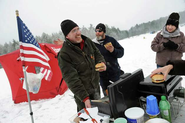 Richard Scott of Averill Park, left, serves up venison burgers and chili to his ice fishing friends during the 30th annual Winter Festival on Saturday, Jan. 24, 2015, at Grafton Lakes State Park in Grafton, N.Y. Scott started fishing at 5 .m. on Long Pond. Joining him are Jerry Walsh of Poestenkill, center, and his wife, Deana Walsh. The event also featured hockey, hikes, games for kids and a polar plunge. (Cindy Schultz / Times Union) Photo: Cindy Schultz / 00030277A
