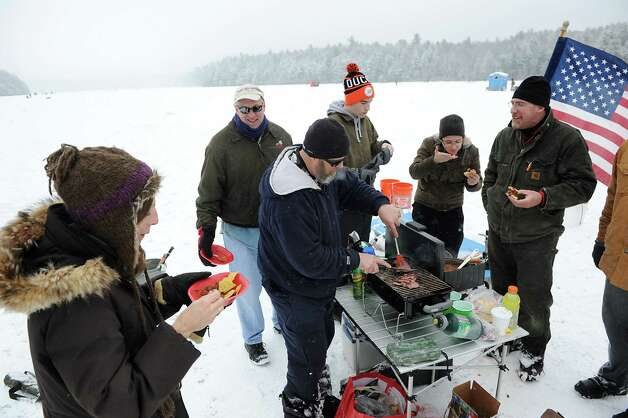 Jerry Walsh of Poestenkill, center, slices a backstrap of venison to serve his ice fishing friends during the 30th annual Winter Festival on Saturday, Jan. 24, 2015, at Grafton Lakes State Park in Grafton, N.Y. Walsh began fishing at 5 .m. on Long Pond. The event also featured hockey, hikes, games for kids and a polar plunge. (Cindy Schultz / Times Union) Photo: Cindy Schultz / 00030277A