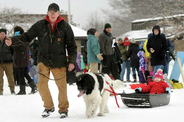 Jim Hussey of Ballston Spa, left, and his Newfoundland, Daisy, take Shea Molitor, 3, of Delmar for a sleigh ride during the 30th annual Winter Festival on Saturday, Jan. 24, 2015, at Grafton Lakes State Park in Grafton, N.Y. The event also featured ice fishing, hockey, hikes, games for kids and a polar plunge. (Cindy Schultz / Times Union) Photo: Cindy Schultz / 00030277A