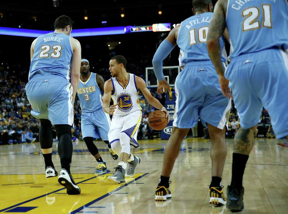 Warriors point guard Stephen Curry, who had eight assists and just one turnover in the game, sizes up a group of Nuggets defenders Monday. Photo: Scott Strazzante / The Chronicle / ONLINE_YES