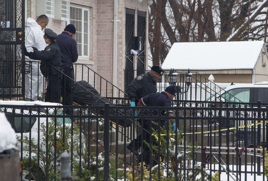New York police officers remove bodies from a house where  a man killed his daughter, his girlfriend and her mother. Photo: ULI SEIT / New York Times / NYTNS
