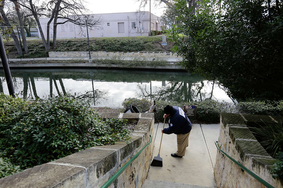 A worker cleans up the sidewalk across the San Antonio River Walk from the former Turner Club building, Jan. 15. Photo: Jerry Lara /San Antonio Express-News / © 2015 San Antonio Express-News