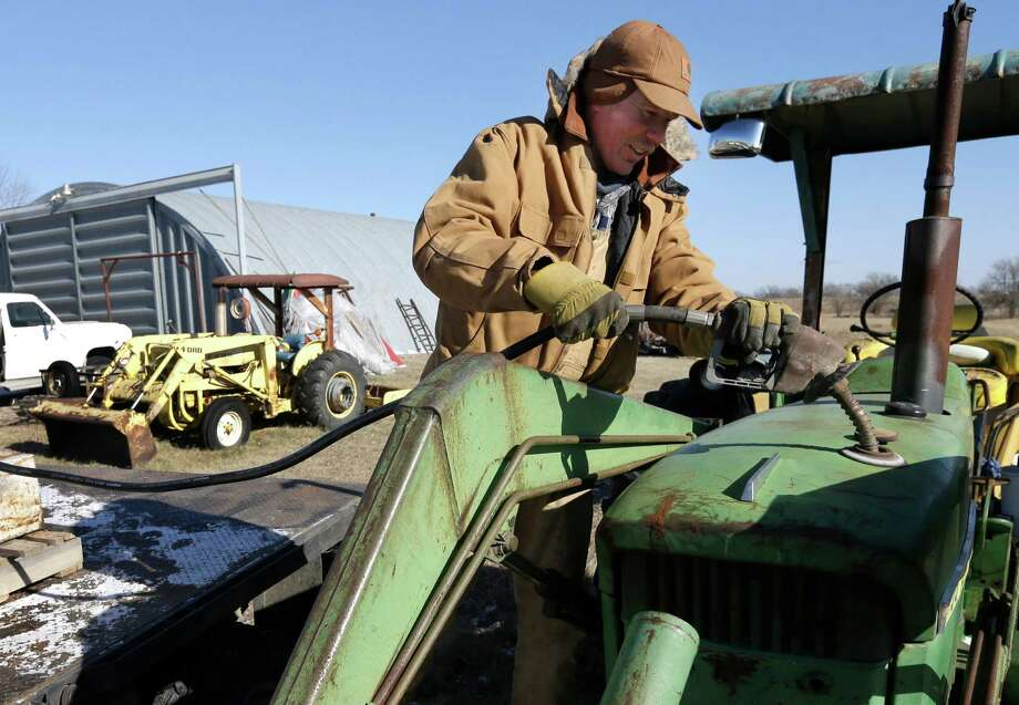 In this Jan. 7, 2015 photo, cattle rancher Cattle rancher Randy Cree fuels up a tractor at his farm near Big Springs, Kan. Because un- taxed diesel and regular gas are cheaper this year, he can afford to fill all his fuel-storage tanks. with the local price of untaxed diesel and regular gasoline both below $2 a gallon, Cree plans to completely fill the two 300-gallon and one 200-gallon tanks.adds fuel to a factor at his farm near Big Springs, Kan. Cree has not been able to afford to fill the fuel tanks at his farm, but with prices below $2.00 he plans completely fill his two 300-gallon and one 200-gallon tanks as soon as he can get a fuel truck to deliver it. (AP Photo/Orlin Wagner) Photo: Orlin Wagner /Associated Press / AP
