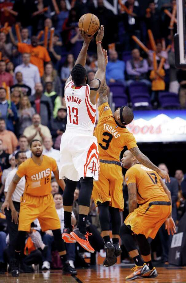 Rockets guard James Harden (13) soars above the Suns' Isaiah Thomas (3) and hits the game-winning field goal as time expires, then savors the moment Friday night in Phoenix. Photo: Ross D. Franklin, STF / AP
