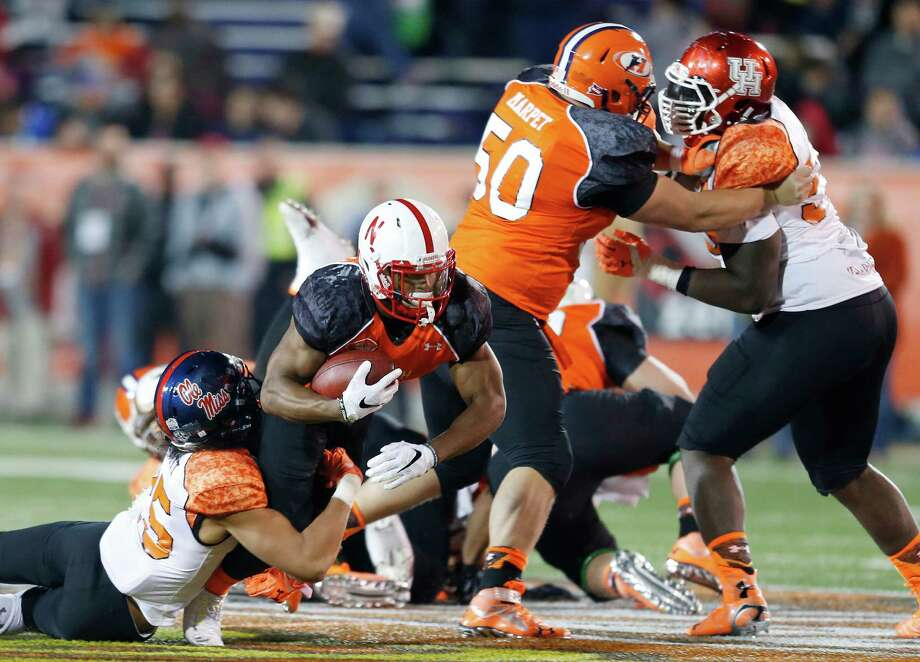 North running back Ameer Abdullah, second from left, of Nebraska, jumps through South's line of defense in the second half during the Senior Bowl NCAA college football game Saturday, Jan. 24, 2015, in Mobile, Ala. Nor(AP Photo/Butch Dill) Photo: Butch Dill, Associated Press / FR111446 AP