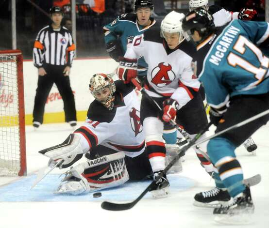 Devils' goaltender Scott Wedgewood, center, works to stop a shot from Sharks' John McCarthy, right, during their hockey game on Saturday, Jan. 24, 2015, at Times Union Center in Albany, N.Y. (Cindy Schultz / Times Union) Photo: Cindy Schultz / 00030124D
