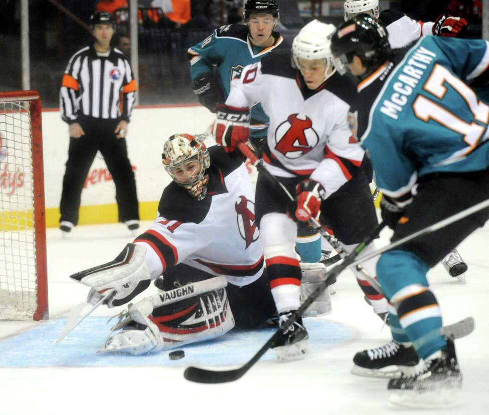 Devils' goaltender Scott Wedgewood, center, works to stop a shot from Sharks' John McCarthy, right, during their hockey game on Saturday, Jan. 24, 2015, at Times Union Center in Albany, N.Y. (Cindy Schultz / Times Union)