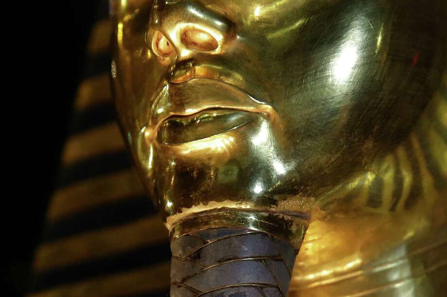A detail of the gold mask of King Tutankhamun showing where the beard is attached is seen in a glass case during a press tour, in the Egyptian Museum near Tahrir Square, Cairo, Egypt, Saturday, Jan. 24, 2015. German restoration specialist, Christian Eckmann, summoned to Cairo to examine the damaged burial mask, spoke at a packed news conference Saturday at the Egyptian museum, saying that epoxy used to glue the mask's beard back on can be removed and the mask properly restored. Eckmann said the beard, which has been detached before from the mask and had likely loosened over the years, was accidentally knocked off last August during work on the relic's lighting. (AP Photo/Hassan Ammar) Photo: Hassan Ammar, STF / AP
