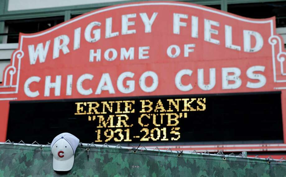 A Cubs hat hangs on the construction fence in front of Wrigley Field in honor of Ernie Banks, who died Friday night at age 83 in Chicago. Photo: Nam Y. Huh, STF / AP