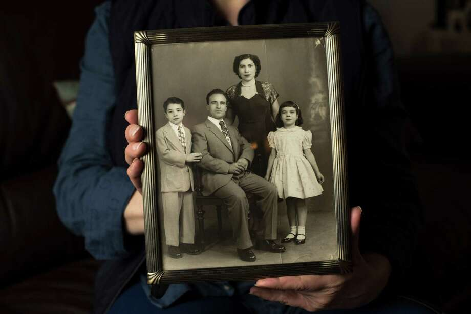 Mary Paloglou holds a family photograph from the 1950s showing her father, Tony Ciccarello, seated, in Garnerville, N.Y., Jan. 17, 2015. A medical examiner ruled that Ciccarello's 2014 death stemmed from a stabbing he suffered near Times Square in the late 1950s, and police have approached the seemingly-quixotic murder investigation — thought to be the oldest ever — as they would any other. (Karsten Moran/The New York Times) Photo: KARSTEN MORAN, STR / New York Times / NYTNS