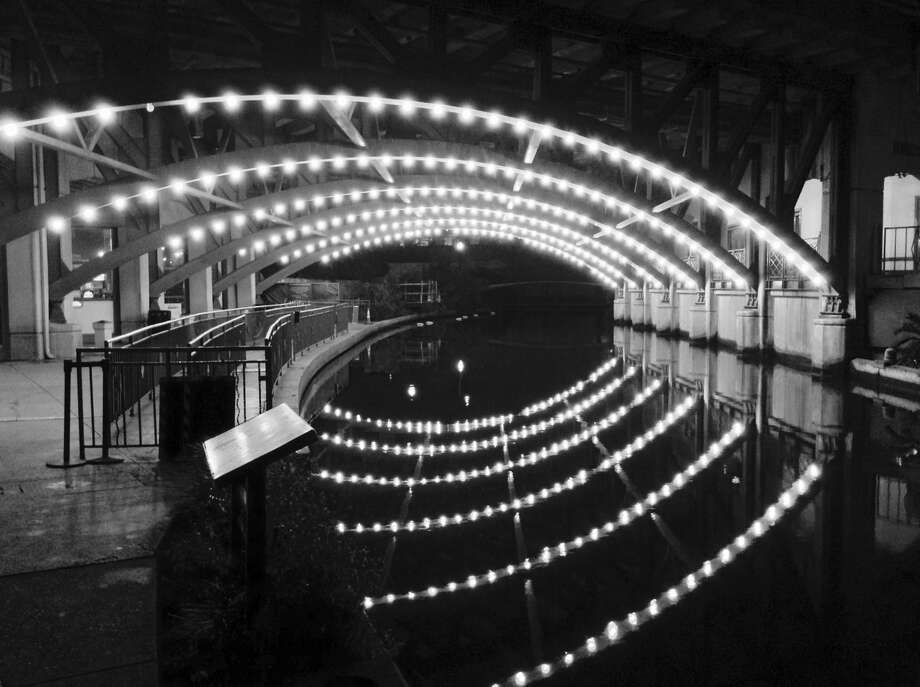 Lights on the underside of a bridge by Rivercenter mall form an interesting pattern when reflected on the water. Photo: Robert Kolarik, San Antonio Express-News