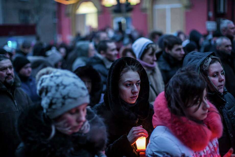 A woman holds a candle at a memorial to those killed in an attack on Donetsk, Ukraine. A leader of the rebels holding that city said the attack would be avenged on multiple fronts, including Mariupol, which was hit Saturday. Photo: Brenda Hoffman /New York Times / NYTNS