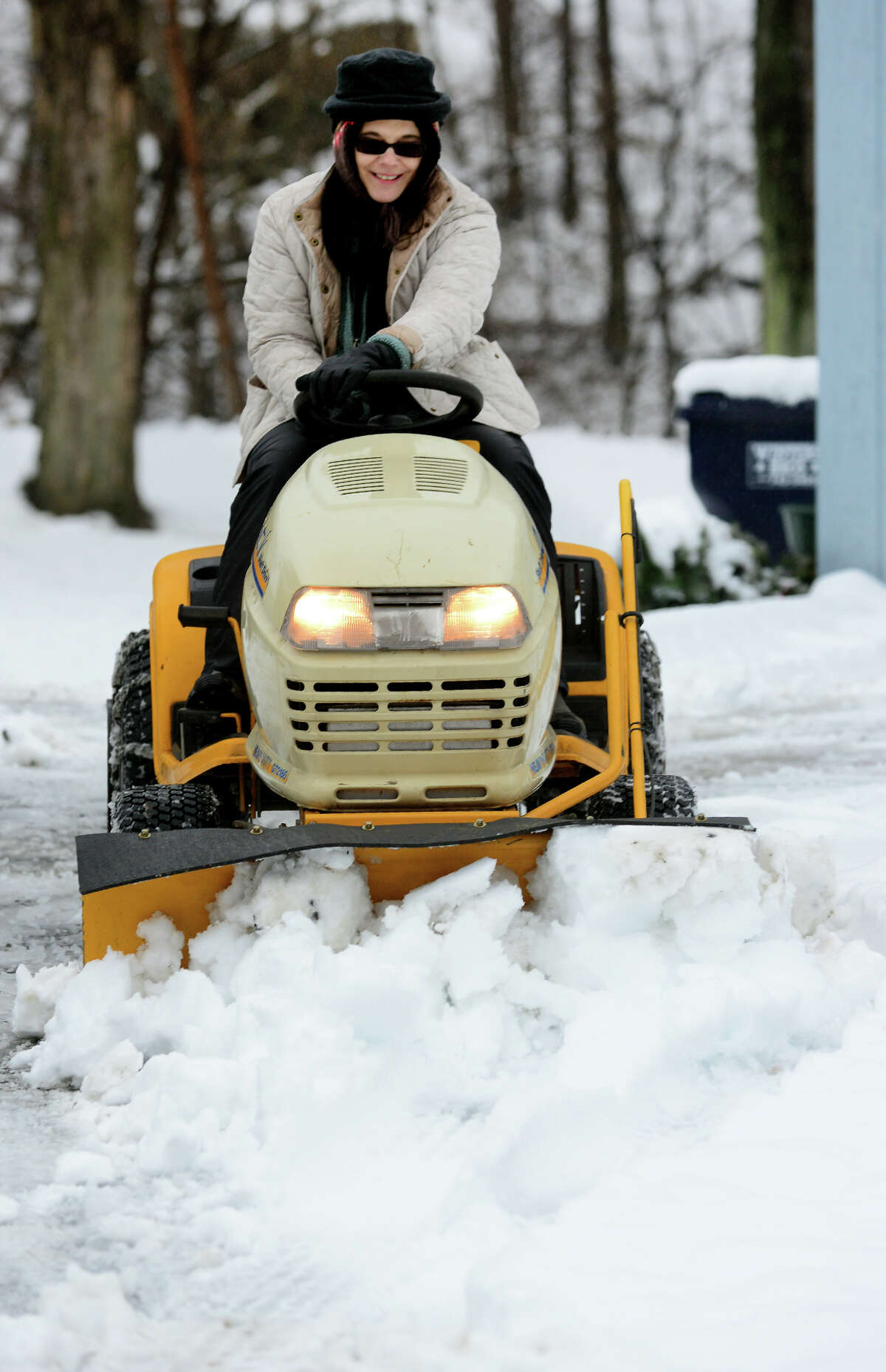 Donna Cherhoniak plows snow with her Cub Cadet plow at her home along Derby Avenue in Seymour, Conn. on Saturday Jan. 24, 2015. Cherhoniak said she got the plow on Craigslist with every attachment available and this was the first time she got to use it.