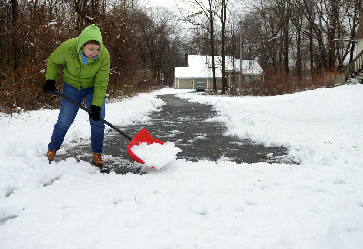 Paula Bajoros shovels the last section of her very long driveway at her home along Shelton Road in Trumbull, Conn. on Saturday Jan. 24, 2015.