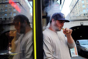 Store manager Sean Trataris smokes an e-cigarette outside Vapor Smoke Shop in downtown San Francisco.