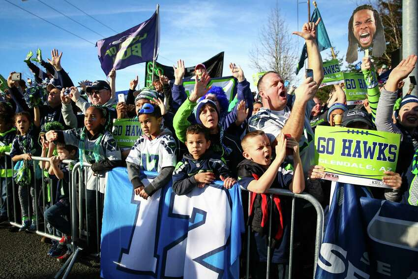 Fans cheer near Seattle-Tacoma Airport as the Seattle Seahawks buses drive past.