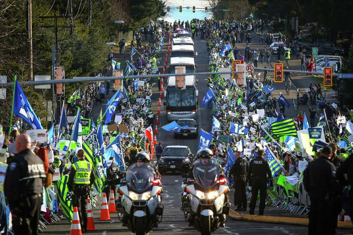 Seattle Seahawks buses travel the route as fans gather along South 188th Street near Seattle-Tacoma Airport to send off the team to the Super Bowl on Sunday, January 25, 2015.