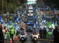 Seattle Seahawks buses travel the route as fans gather along South 188th Street near Seattle-Tacoma Airport to send off the team to the Super Bowl. Photographed on Sunday, January 25, 2015.