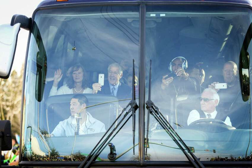 Seattle Seahawks coach Pete Carroll watches from the front seat as Seahawks buses travel the route along South 188th Street near Seattle-Tacoma Airport.