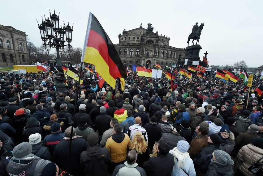 Demonstrators wave flags during a rally of the group Patriotic Europeans against the Islamization of the West, or PEGIDA, in Dresden, Germany, Sunday, Jan. 25, 2015.