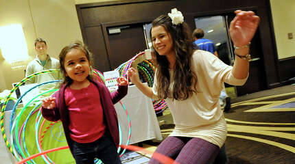 President and instructor with Luluhoops Lauren Gee, right, encourages Liana Varela, 2, on the Hula Hoops during the Celebrity Baby Trends' family fun day at the Hyatt Regency in Greenwich, Conn., on Sunday, Jan. 25, 2015. The event featured games, entertainment