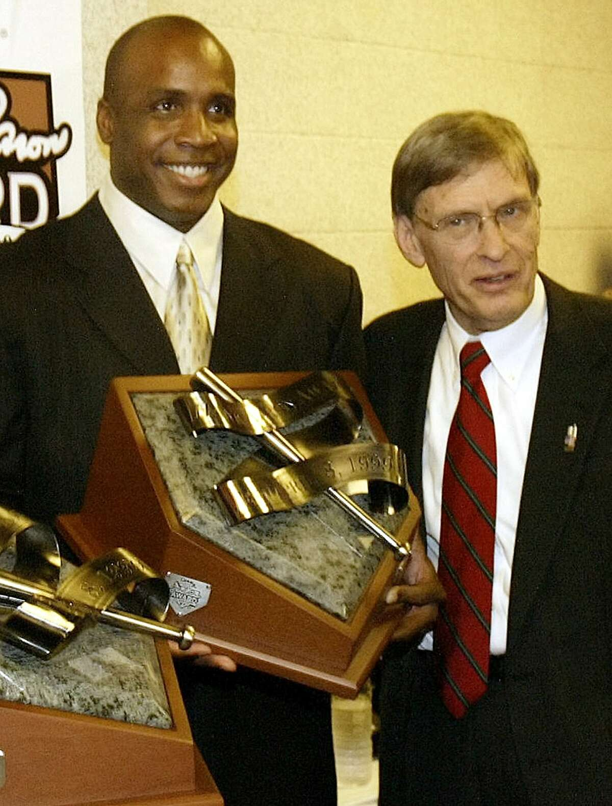San Francisco Giants' Barry Bonds, left, holds the National League Hank Aaron award with Commissioner Bud Selig, right, during a ceremony before Game 4 of the World Series in this Oct. 27, 2004 photo in St. Louis.