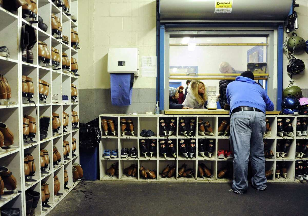 Rink employee Chris Belmont assists skaters with their skates at the Dorothy Hamill Ice Rink in Greenwich, Conn. Sunday, Jan. 25, 2015. Temple Sholom held its annual