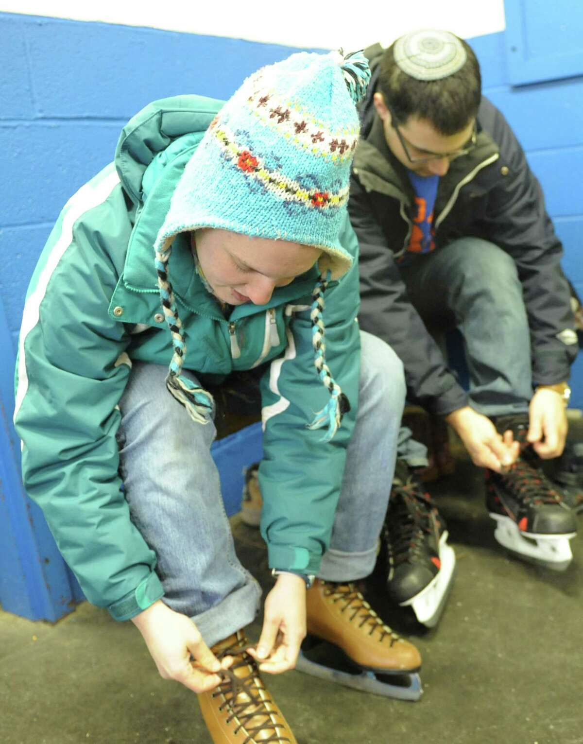 Temple Sholom members Naomi Scheinerman, of New Haven, and Yoni Nadiv, of New York, put on their skates at the Dorothy Hamill Ice Rink in Greenwich, Conn. Sunday, Jan. 25, 2015. Temple Sholom held its annual