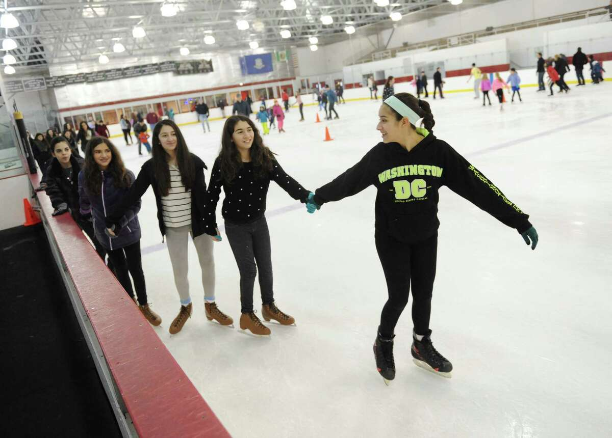 13-year-old friends, from right to left, Isabella Ramos, of Port Chester, N.Y., Madeline Loiaroni, of Port Chester, N.Y., Victoria Amador, of Greenwich, Sara Tarascio, of Port Chester, N.Y., and Brianna Ayala, of Port Chester, N.Y., skate together at the Dorothy Hamill Ice Rink in Greenwich, Conn. Sunday, Jan. 25, 2015. Temple Sholom held its annual