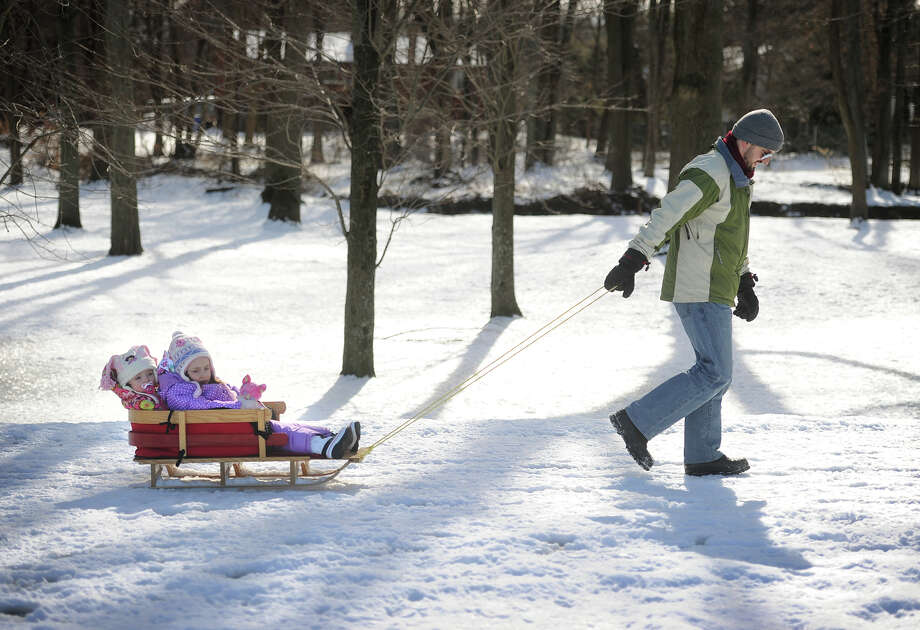 Jacques Begin, of Trumbull, pulls daughters Vivienne, 1, and Genevieve, 3, on a sleigh ride through the snow at Twin Brooks Park in Trumbull, Conn. on Sunday, January 25, 2015. Photo: Brian A. Pounds / Connecticut Post