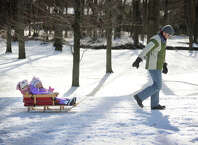 Jacques Begin, of Trumbull, pulls daughters Vivienne, 1, and Genevieve, 3, on a sleigh ride through the snow at Twin Brooks Park in Trumbull, Conn. on Sunday, January 25, 2015.