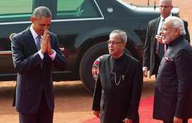 President Obama makes a traditional Indian greeting gesture as Indian President Pranab Mukherjee (center) and Prime Minister Narendra Modi welcome him to the presidential palace in New Delhi.