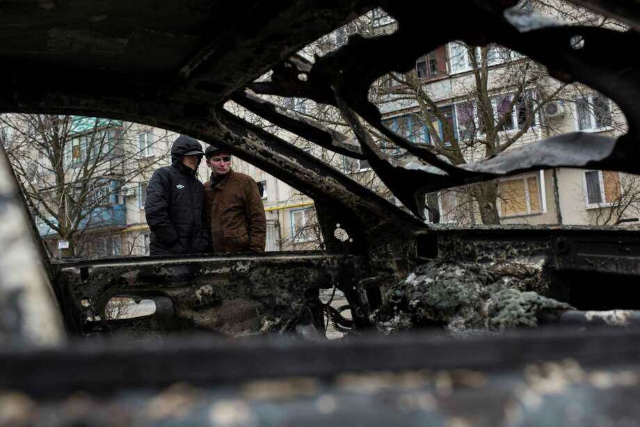 Residents look over a burned car in Vostochniy district of Mariupol, eastern Ukraine. Rocket fire slammed into a market, schools, homes and shops Saturday, killing at least 30 people. Photo: Evgeniy Maloletka / Associated Press / AP