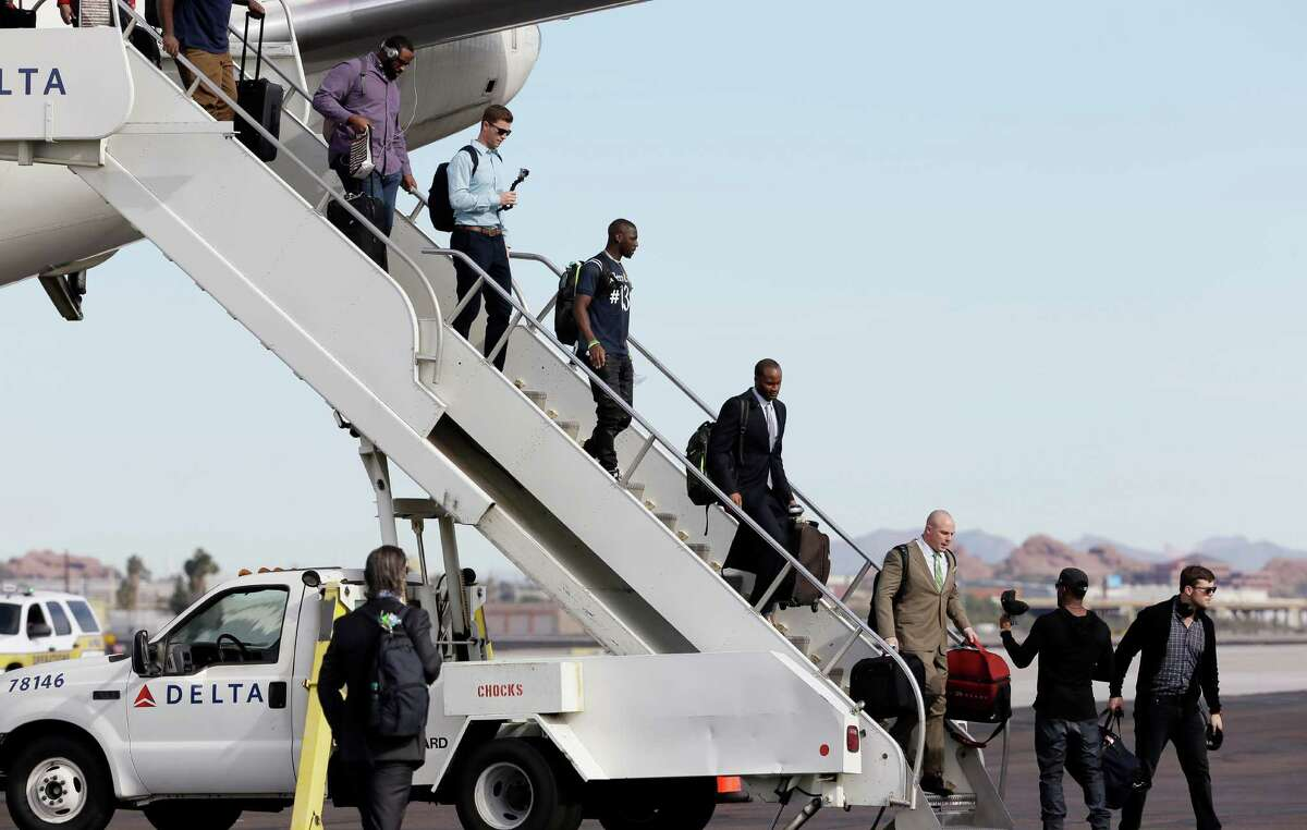 Seattle Seahawks players arrive at Sky Harbor Airport for NFL Super Bowl XLIX football game Sunday, Jan. 25, 2015, in Phoenix. The Seahawks play the New England Patriots in Super Bowl XLIX on Sunday, Feb. 1, 2015.
