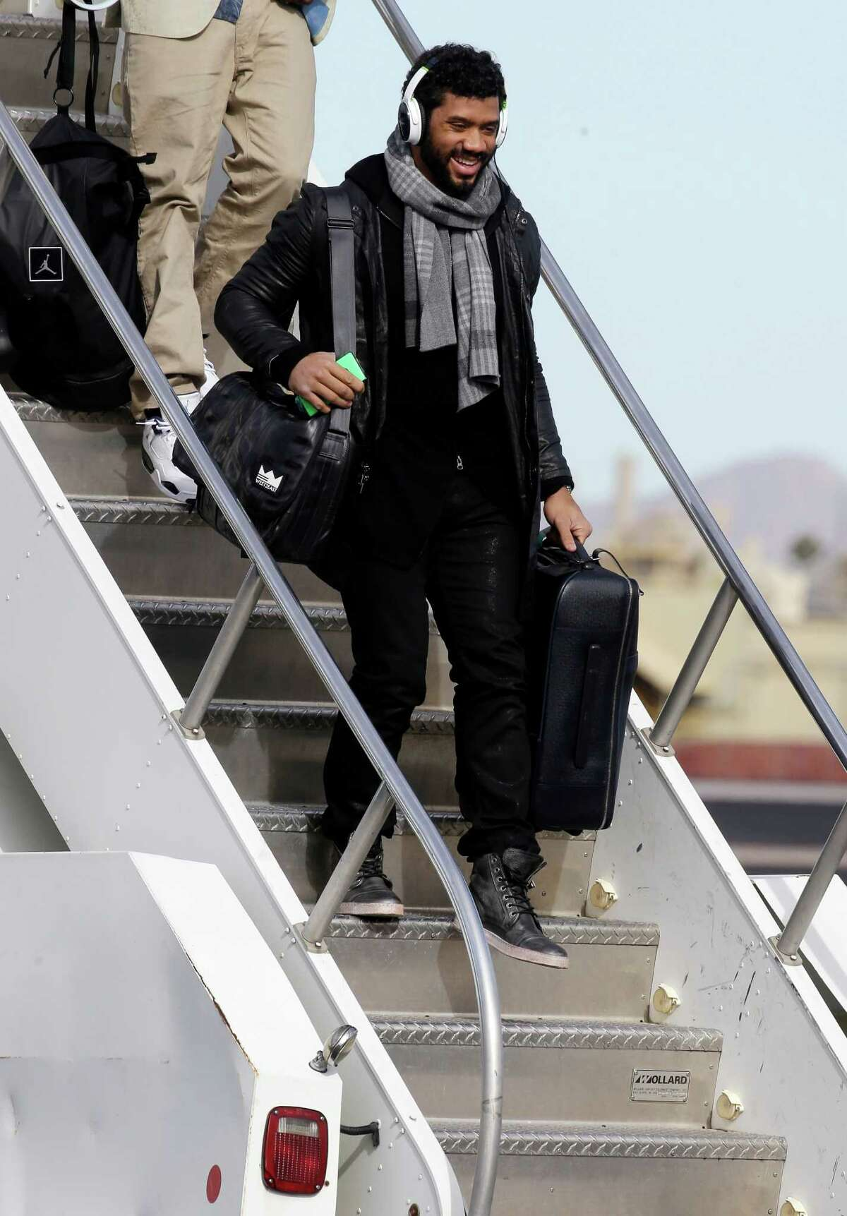 Seattle Seahawks' Russell Wilson smiles as he arrives at Sky Harbor Airport for NFL Super Bowl XLIX football game Sunday, Jan. 25, 2015, in Phoenix. The Seahawks play the New England Patriots in Super Bowl XLIX on Sunday, Feb. 1, 2015.