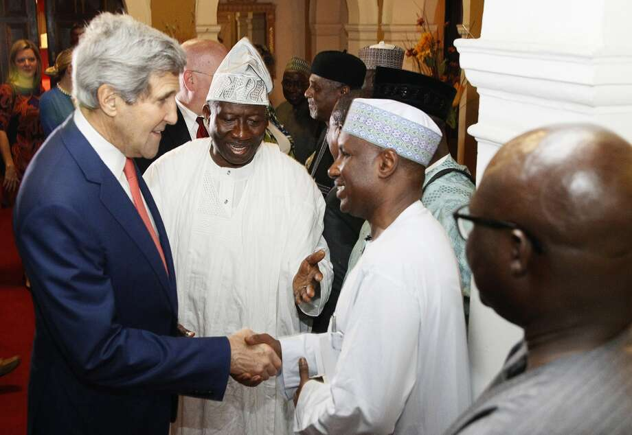 U.S. Secretary of State John Kerry (left) greets a government official during his meeting with Nigeria's President Goodluck Jonathan (center) in Lagos, 1000 miles south of the attacks by Islamic militants. Photo: AKINTUNDE AKINLEYE / AFP / Getty Images / AFP