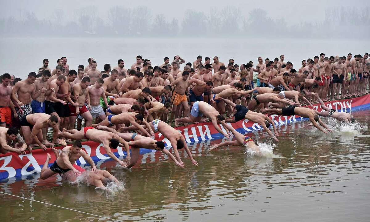 Swimmers jump on January 19, 2015 in the cold waters of the Danube river on Epiphany day as they compete to reach for the floating cross in Zemun, near Belgrade. It is believed that the man who grabs the cross first will be healthy throughout the New Year.