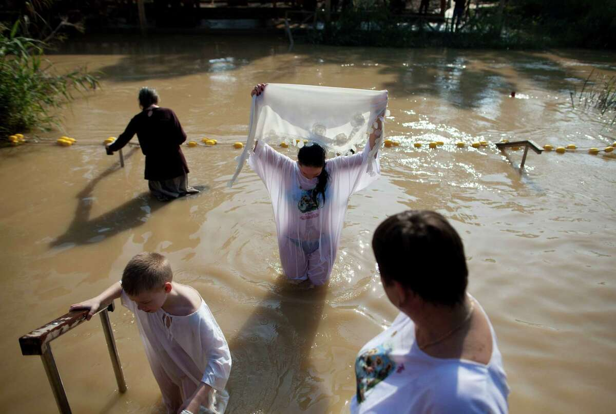 Orthodox Christians pilgrims are baptized during an Epiphany celebrations in the Jordan River at the Qasir al-Yahud baptismal on January 18, 2015 near Jericho, West Bank. Pilgrims gathered for the annual celebration at the site that the Eastern churches believes Jesus was baptised by John.