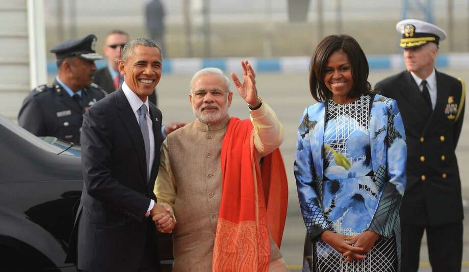 President Barack Obama greets Indian Prime Minister Narendra Modi as first lady Michelle Obama stands with them upon arrival at the Palam Air Force Station in New Delhi, India. Photo: Associated Press / AP