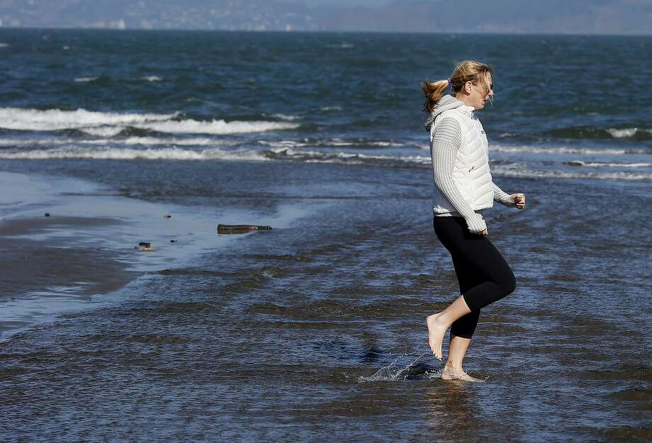 Ali Hartley demonstrated the technique for dashing across the water to her son at East Beach. Thousands flocked to San Francisco beaches Sunday January 25, 2015. At East Beach near Crissy Field many admitted it was colder than weather reports indicated. Photo: Brant Ward, The Chronicle