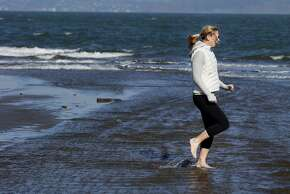 Ali Hartley demonstrated the technique for dashing across the water to her son at East Beach. Thousands flocked to San Francisco beaches Sunday January 25, 2015. At East Beach near Crissy Field many admitted it was colder than weather reports indicated.