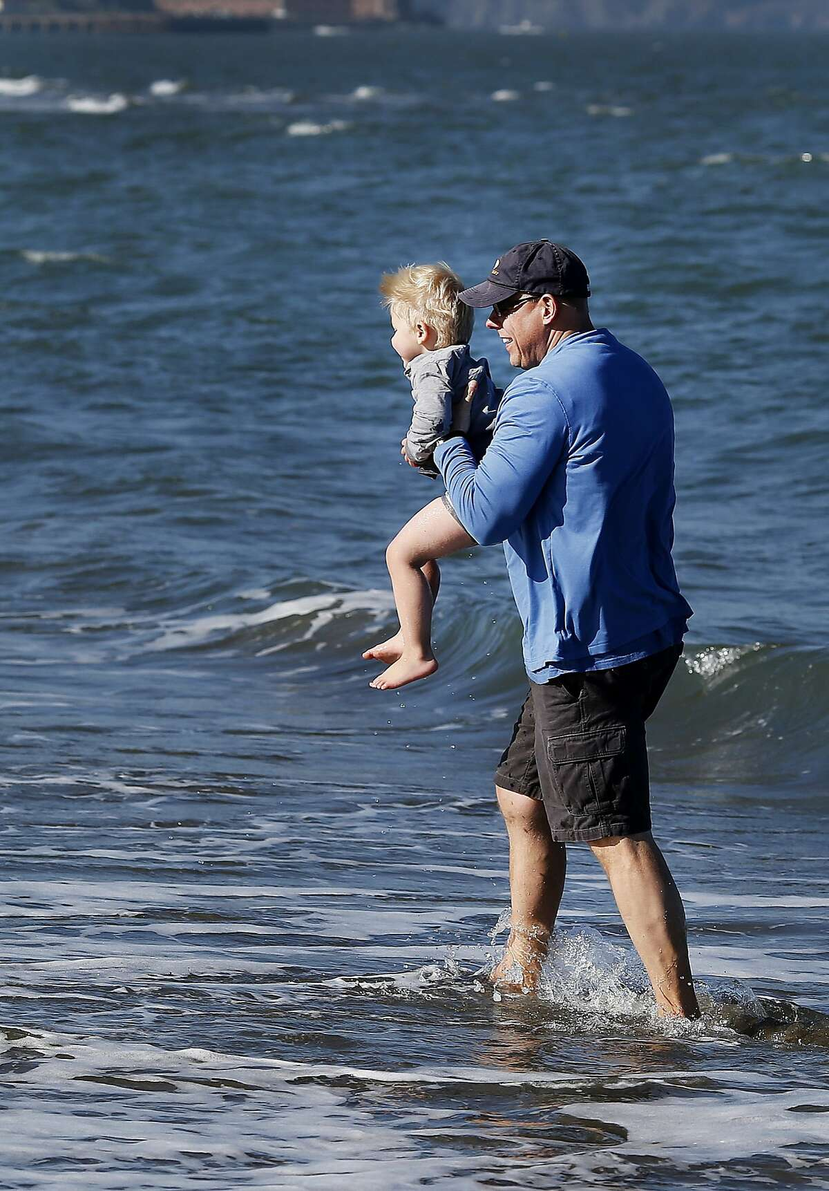 Three year old Cooper Mittag got a ride from father Rod Mittag out of the surf at East Beach. Thousands flocked to San Francisco beaches Sunday January 25, 2015. At East Beach near Crissy Field many admitted it was colder than weather reports indicated.