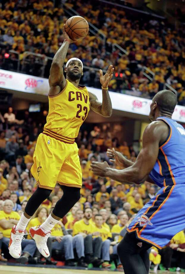 Cleveland's LeBron James lofts a shot over Oklahoma City's Serge Ibaka on his way to 34 points. Photo: Mark Duncan / Associated Press / AP