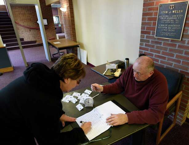 Richard Savage, right, checks people in at the Guilderland Town Hall Tuesday afternoon Jan. 20, 2015 in Guilderland, N.Y.    (Skip Dickstein/Times Union) Photo: SKIP DICKSTEIN / 00030280A