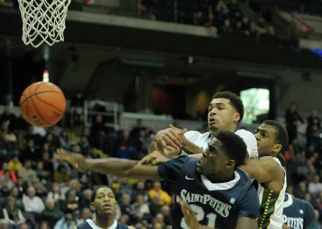 Jimmy Paige, foreground, of Saint Peter's and Javion Ogunyemi of Siena battle for a rebound during their game at the Times Union Center on Sunday, Jan. 25, 2014, in Albany, N.Y.    (Paul Buckowski / Times Union) Photo: Paul Buckowski / 00030241B