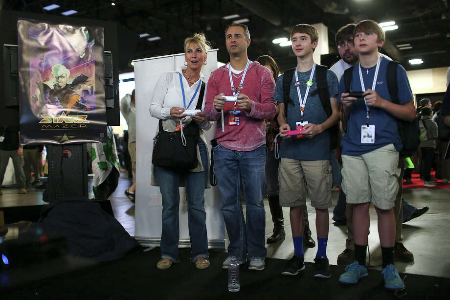 """From left, Joni Baker, Jeff James and his sons, Hunter and Jonathan James play """"Sportsball,"""" during Pax South 2015 gaming convention at the Henry B. Gonzalez Convention Center, Sunday, Jan. 25, 2015. Photo: JERRY LARA, Staff / San Antonio Express-News / © 2015 San Antonio Express-News"""