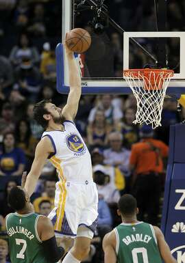 Andrew Bogut (12) dunks the ball in the first half. The Golden State Warriors played the Boston Celtics at Oracle Arena in Oakland, Calif., on Sunday, January 25, 2015.